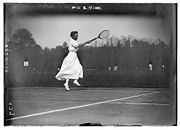 A woman in all white attire is hitting a forehand with the tennis racket in the right hand, which it is a black and white photograph