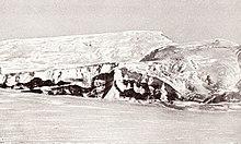 Longa glacia montkresto kun du pintoj, leviĝante de plata neĝebenaĵo