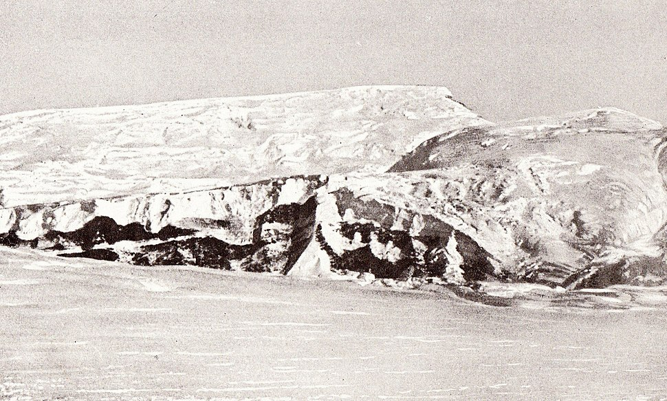A long icy mountain ridge with two peaks, rising from a flat snow plain