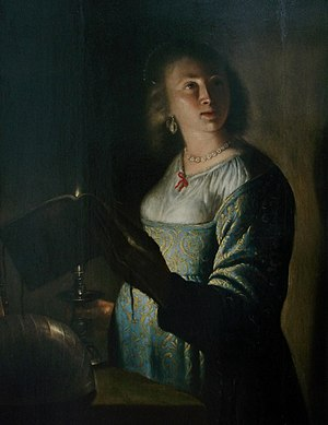 Isaac de Jouderville - Young women with book by candlelight
