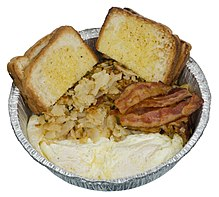 Metal container of hash browns, eggs, bacon, and slices of white bread.