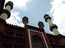 A mosque in red stone, having two tall and two short minarets