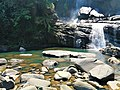 Natural waterfall with rounded rocks and water stream.jpg