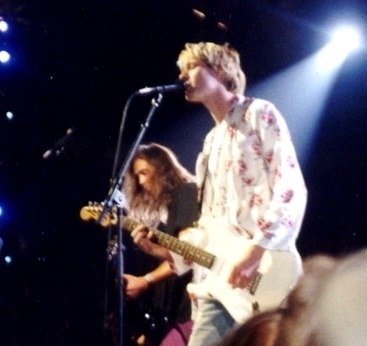 Two members of a rock band, Nirvana, pictured onstage at a show for the MTV Video Music Awards. A male singer and guitarist, Kurt Cobain, is playing electric guitar and singing into a microphone.