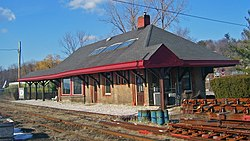 A brick building seen from its right front. It has a peaked black roof with red trim and a broad overhang. In front of it are rusted railroad tracks. Two old green passenger cars are behind it to the left.