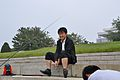 One of our North Korean guides on a cigarette break as he waits for hungry fish (10058658683).jpg