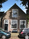 foto van Huis met puntgevel, goede schuiframen, bovenlicht en deur met kussenpaneel