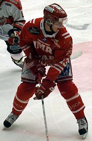 An ice hockey player stands partially crouched, while looking to his left. He is wearing a red helmet and uniform.