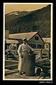 Photographic postcard of a cook standing with a cat resting on a wharf probably in Alaska, United States of America (9927421006).jpg