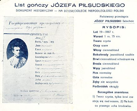 "1928 reproduction of an 1887 Russian wanted poster for Pilsudski, distributed (presumably by his political enemies) ""on the 10th anniversary of Poland's independence"":  Translation ""State criminal  JOZEF PILSUDSKI, nobleman DESCRIPTION: Age 19 (1887) Height 1.75 m (5.74 ft). Face clear Eyes grey Hair dark-blond Sideburns light-blond, sparse Eyebrows dark-blond, fused Beard dark-blond Mustache light-blond Nose normal Mouth normal Teeth missing some Chin round Distinctive marks: 1) clear face, with eyebrows fused over nose, 2) wart at the end of right ear"" Pilsudski wanted.jpg"
