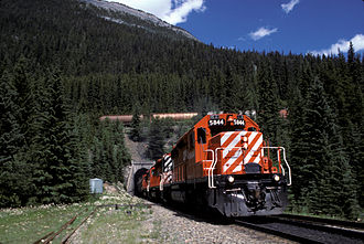 """Big Hill - Lower portal of """"Number Two"""" tunnel, Spiral Tunnels, Field, British Columbia. The locomotives are passing under the train they are pulling."""