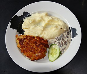 Pozharsky cutlet - A Pozharsky cutlet served with mashed potatoes, mushroom sauce and sliced cucumber