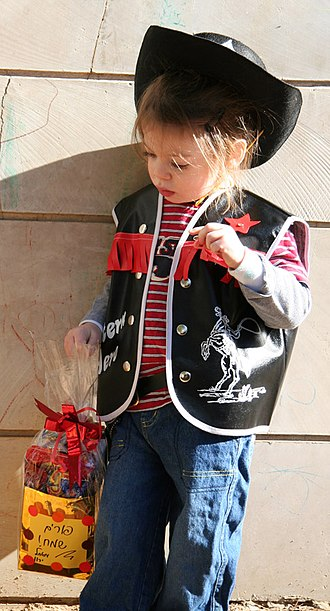 Purim - Israeli child dressed up as a cowboy while holding his Purim basket of candies (mishloach manot)