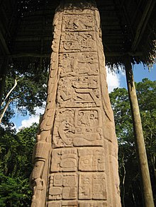 The side of a stela, divided into square panels containing sculpted hieroglyphs