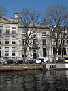 foto van Dubbel huis met drie traveeën brede zandstenen gevel met middenrisaliet en geblokte hoeklisenen, versierde middentravee waarin marmeren balcon
