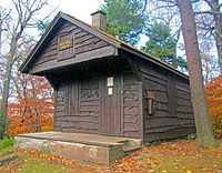 "A small maroon-colored wooden cabin with its roof overhanging the front porch. On that section is a sign that says, in gold lettering, ""Red Hill, 2,990 feet"". Behind it are woods, partly green and partly in fall color"