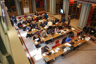 Photo shows an elevated view of a large library with many people sitting at computers editing Wikipedia