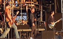 A rock band, the Stone Temple Pilots, performing onstage. From left to right, a bass guitarist, singer and guitarist are shown.