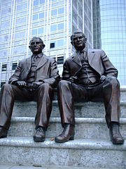"""Bronze of the Mayo brothers, """"Dr. Will"""" and """"Dr. Charlie"""", with the Gonda Building of Mayo Clinic behind them."""
