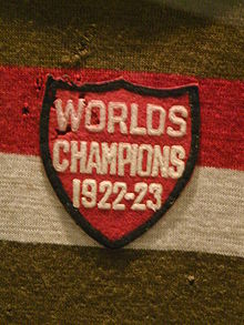 "A red shield-shaped cloth crest with the inscription ""Worlds Champions 1922–23"" sewn onto a gold red and white striped sweater"