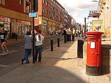 A view looking down Division Street in Sheffield, with a postbox, a Spar shop and pedestrians