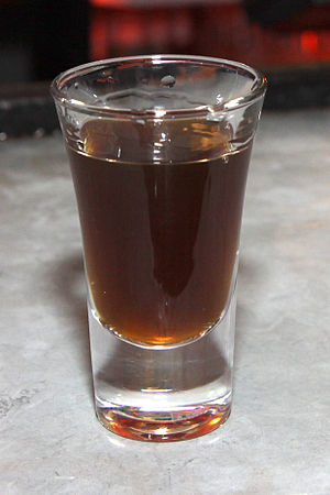 English: A shot glass filled with alcohol and ...