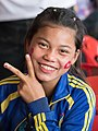 Smiling adolescent girl giving V-sign.jpg