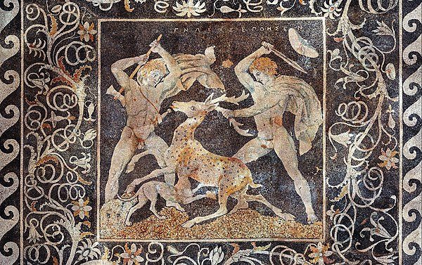 The Stag Hunt Mosaic, c. 300 BC, from Pella; the figure on the right is possibly Alexander the Great due to the date of the mosaic along with the depicted upsweep of his centrally-parted hair (anastole); the figure on the left wielding a double-edged axe (associated with Hephaistos) is perhaps Hephaestion, one of Alexander's loyal companions. Stag hunt mosaic, Pella.jpg
