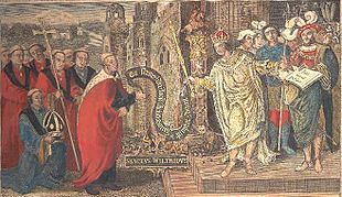 A crowned man hands a scroll to a tonsured man. The crowned man is standing on the steps of a building, surrounded by other men. The man receiving the scroll stands in front of the building, also surrounded by other men.
