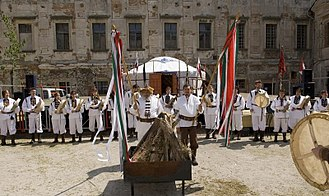 Hungarian Native Faith - Gathering of a Hungarian Native Faith group for the performance of a ritual. The two leading figures hold ritual spears with strips of cloth of the colours of the flag of Hungary tied near the tips.