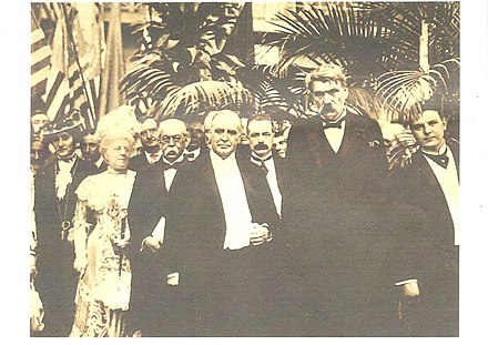 "The ""last posed photograph"" of President McKinley, in the Government Building on September 5, 1901. Left to right: Mrs. John Miller Horton, Chairwoman of the Entertainment Committee of the Woman's Board of Managers; John G. Milburn; Manuel de Azpiroz, the Mexican Ambassador; the President; George B. Cortelyou, the President's secretary; Col. John H. Bingham of the Government Board. The ""Last Posed Photograph"" of President McKinley.In the Government Building on September 5, 1901..jpg"