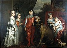 """Five children are dressed in 16th century clothing, two girls in white to the left and a boy in red in the centre. To the right is a girl sitting holding a baby in her arms. A large brown mastiff dog sits in the middle next to the boy and a small white and brown spaniel is in the bottom right."""