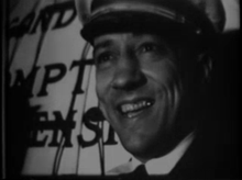 Face only portrait of man in his thirties, smiling, wearing dress Navy hat and uniform with tie. Writing visible at left.