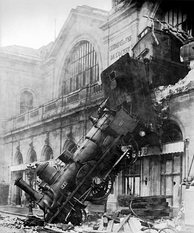 Ninenteenth century train crash with steam locomotive going through the wall of an end station.