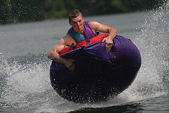 Tubing (recreation) - Towed tubing on a lake. Riders can often become airborne while passing over waves or wake from the motor boat or personal watercraft.