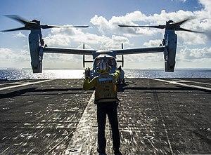 U.S. Navy Aviation Boatswain's Mate (Handling) 1st Class Kerry Carter, aboard the aircraft carrier USS George Washington (CVN 73), signals to the pilot of a Marine Corps MV-22 Osprey tiltrotor aircraft assigned 131118-N-IP531-240.jpg