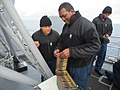 U.S. Navy Interior Communications Electrician 1st Class Totakeo Praylow, left, and Logistics Specialist 1st Class Reggie Telebrico inspect .50-caliber ammunition prior to a live-fire exercise aboard the guided 140115-N-NZ411-002.jpg