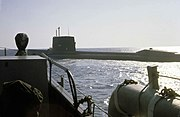 Color photograph depicting the port side of a large surfaced nuclear submarine taken from the bow of an escorting surface ship as the submarine leaves port.