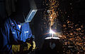 US Navy 021028-N-7222M-002 A sailor welds a steel piece of iron which will be used to make repairs to the ship's hull.jpg