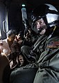US Navy 050104-N-6817C-153 Air crewman Matt Gardner, of Phoenix, Az., holds the IV bottle of an ill Indonesian woman during a humanitarian aid mission to Aceh, Sumatra, Indonesia.jpg