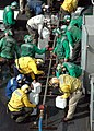 US Navy 050106-N-4336M-285 Crew members aboard USS Abraham Lincoln (CVN 72) fill jugs with purified water from a Potable Water Manifold.jpg