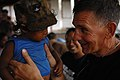 US Navy 080823-N-7544A-151 Lt. Cmdr. Paul Wickard holds a child during a medical exam.jpg