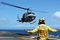 US Navy 081001-N-4856C-034 Aviation Boatswain's Mate (Handling) 3rd Class Demetrius Davis signals to a UH-1.jpg