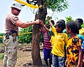 US Navy 110707-N-EF657-133 Chief Petty Officer Timothy Taylor shakes hand with children at a water well project.jpg