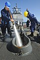 US Navy 110822-N-YM590-027 Seaman Apprentice Todd McBurnett Jr., left, uses a fire hose to clean debris off the anchor chain aboard the guided-miss.jpg