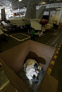 US Navy 120124-N-DR144-388 Airman Recruit Travis Nesbit works inside a cardboard shipping container to control dust and flying debris as he sands o.jpg