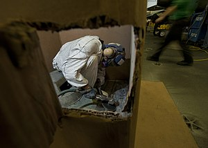 US Navy 120124-N-DR144-419 Airman Recruit Travis Nesbit works inside a cardboard shipping container to control dust and flying debris as he sands o.jpg