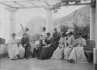 Norman Douglas - Visiting the Villa Torricella Capri (October 1906). Norman Douglas sits in the middle, leaning against the column.