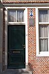 foto van Huis met gepleisterde lijstgevel, aan de hoeken ingezwenkt. Dakkapel
