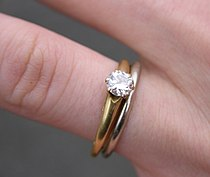 A white gold wedding ring and a single-diamond, gold-banded engagement ring.
